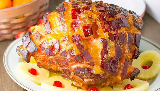 Pineapple-glazed ham is covered in pineapple jam and then baked in the oven until skin is crisp and brown.
