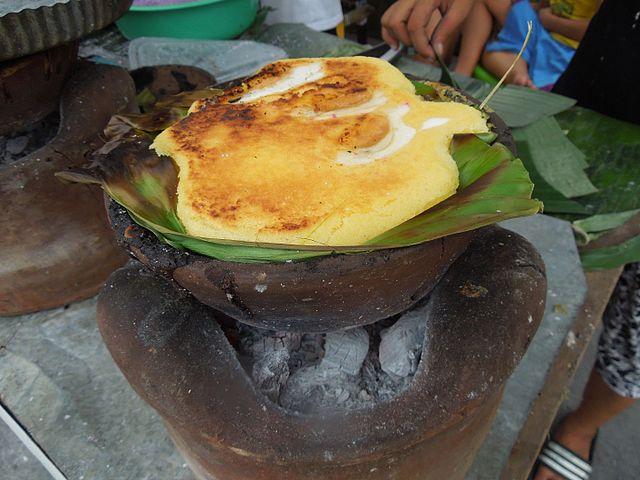 Bibingka is a Filipino cake made with ground glutinous rice, coconut milk and eggs, lined with banana leaves, and cooked in clay pots. Photo by Judgefloro.