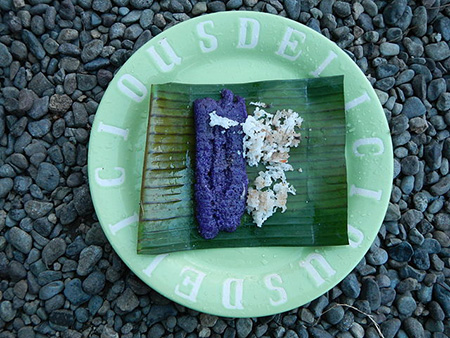 Puto bumbong, a purple-coloured sticky rice cake shaped like small logs and flavoured with brown sugar, margarine or butter, and fresh grated coconut, is sold outside churches in December. Photo by Ramon FVelasquez.